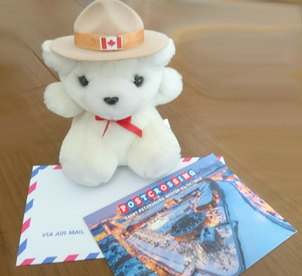 エアメール封筒とカナダこ国旗を付けたクマのぬいぐるみ